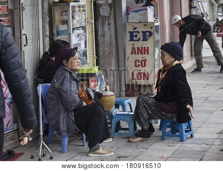 Hanoi, Vietnam - March 9, 2017:  People eating Vietnamese traditional noodle soup Pho or drinking coffee, tea or juice fruit on sidewalk. Eating on pavement is common in Hanoi