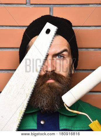 Bearded Worker Holding Various Building Tools With Serious Face