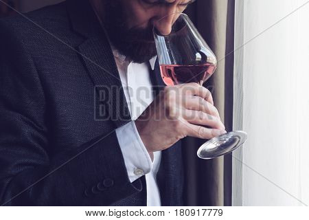 horizontal close up of a Caucasian man with beard black suit and white shirt tasting a glass of rose wine