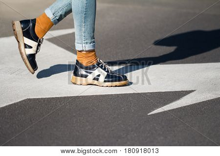 side view close up of a fashionable young woman legs wearing black shoes and blue jeans walking from left to right on the street natural daylight