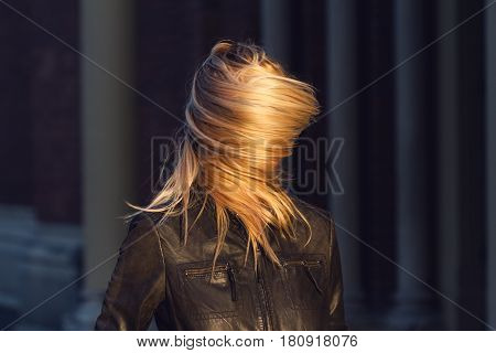 young blonde woman with waving hair completely covering her face wearing a black leather jacket natural light dark background motion blur