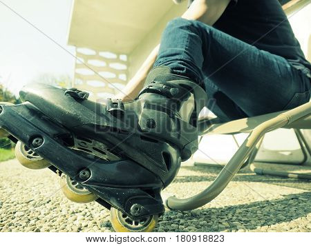 Wide angle close up shot of a man putting on roller skates natural sunlight vintage color toned