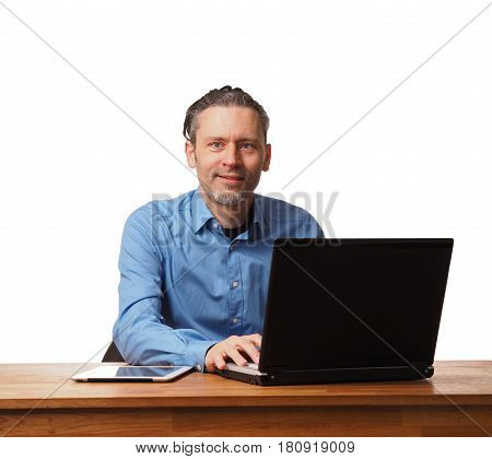 Handsome business man working on an office table with a laptop