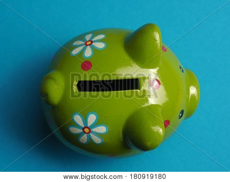 Close up shot of a green cute ceramic piggy bank view from above financial money savings concept