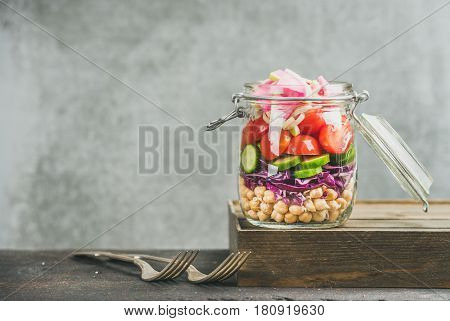 Healthy take-away lunch jar. Vegetable and chickpea sprout vegan salad in glass jar, grey concrete wall background, copy space, selective focus. Clean eating, vegetarian, detox, raw, dieting concept