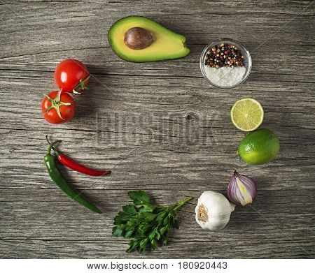 Fresh ingredients for Avocado guacamole on wooden table