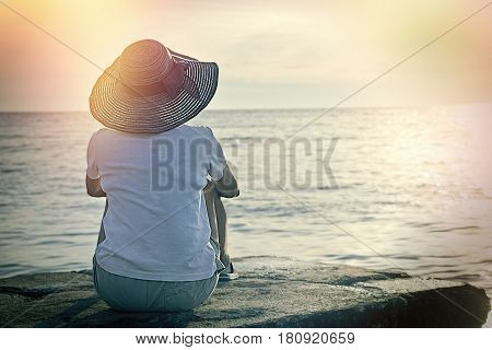 Soft focus on a woman who enjoys the view, relaxing on the beach in the evening sunset - enjoys in vacation, enjoys in landscape