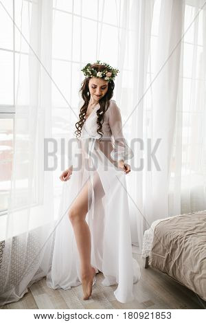Young beautiful bride in a beautiful wedding dress with a wreath of flowers on her head. Wedding. Bride's morning.
