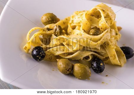 Portion Of Tagliatelle With Green Pesto And Capers And Olives