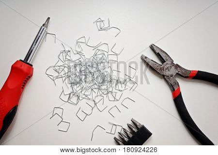 Pliers screwdriver and staples on a white table top view