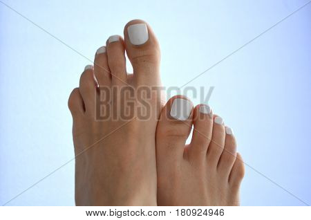 Female beautiful legs - white pedicure, extensible nails and items for pedicure