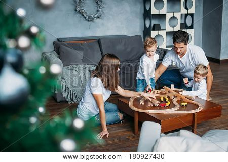 happy family mother father twins boys playing with toy railway road at home on table christmas