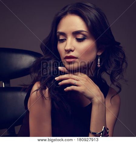 Beautiful Young Makeup Model Loking Down In Fashion Watch And Pink Earring On Dark Shadow Background