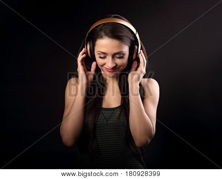 Beautiful Enjoying Young Woman Listening The Music In Wireless Headphone With Closed Eyes On Dark Bl