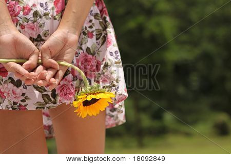 Asian lady hold flower behind her back