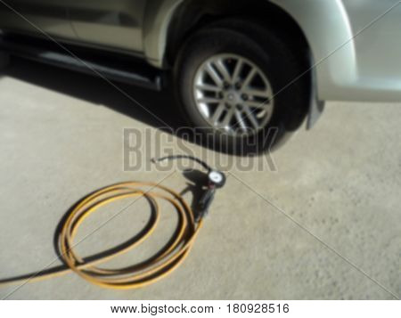 Blurred photo of tire Infiltrator to put air into the tire,Blurred photo can be background,Checking air pressure and filling air in the tires of his modern car.