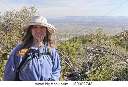 A Smiling Woman Hiking in the Mountains with the Wind Blowing Her Hair