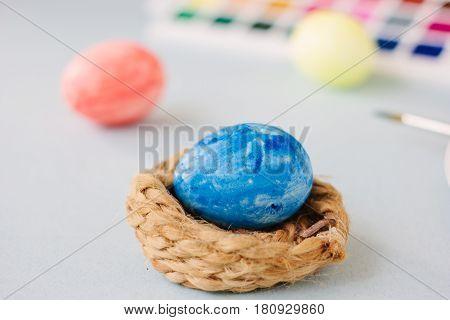 Deep Blue Easter Egg On Nest Over Bright Background.