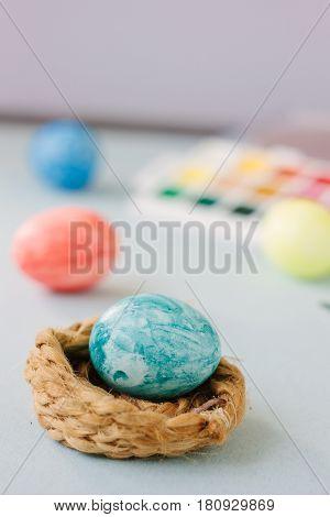Light Blue Color Easter Egg On Nest Over Bright Background.
