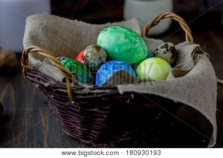 Colored Easter Eggs On Basket Over Rustic Table.
