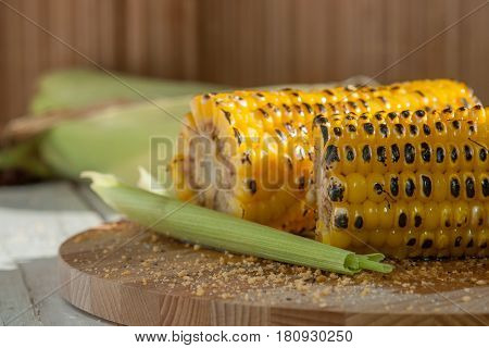 Two Grilled Corn On A Wooden Plate