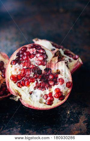 Half of pomegranate fruit on black rustic background