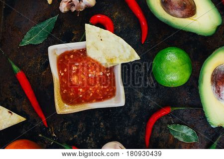 Hot Mexican Salsa Whith The Nacho Chips Surrounded By Ingredients - Tomatoes, Chili Peppers, Lime.
