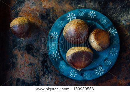 Fresh Chestnuts On Blue Plate