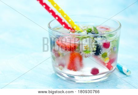 Refreshing water with frozen in ice cubes berries fruits and flowers in glass with straws