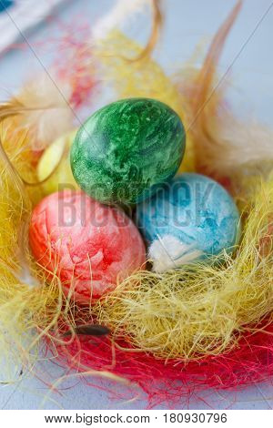 Colored Easter Eggs On Vivid Nest Over Bright And Airy Background.