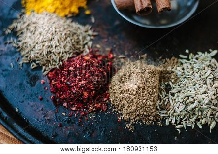 Set Of Different Spices Over Black Metal Plate.