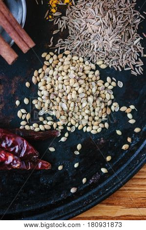 Coriander Seeds On Black Metal Plate Surrounded By Spices.