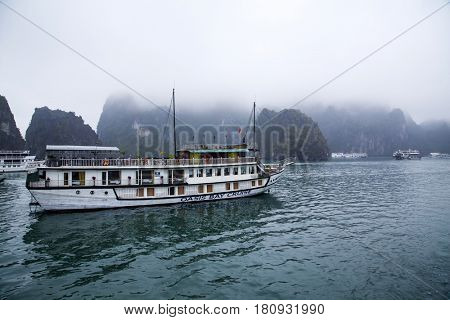 Ha Long Bay, Vietnam - March 11, 2017: Exotic cruise boat with red sails carrying tourists in Ha Long Bay. The popular destination is recognized as a UNESCO World Heritage Site.