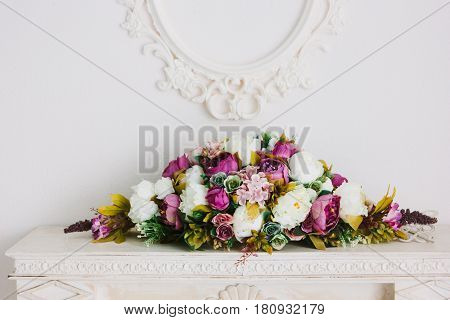 Bouquet of flowers over white fireplace in classic interior.