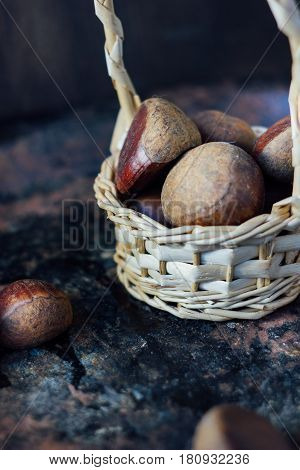 Fresh Chestnuts In Basket Over Black Rustic Surface.