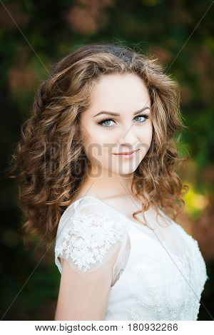 Portrait of young sexy girl. She has curly hair and dressed in a white dress