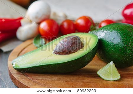 Half Of Avocado On Wooden Board With Lime And Tomatoes.