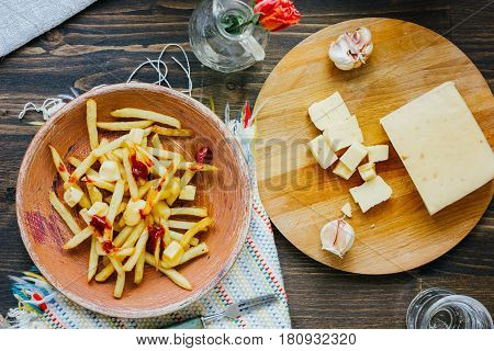 Poutine Fries On Black Surface. Canadian Dish With Potatoes, Cheese And Sauce.
