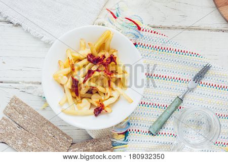 Poutine Fries With Tomato Sauce And Cheese On White Table.