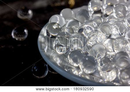 Balls of hydrogel on white plate over black metal background.