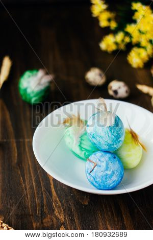 Blue, Yellow And Green Color Easter Eggs On Ceramic Bowl Over Rustic Table.