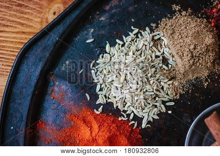 Caraway Seeds Surrounded By Spices On Black Rustic Plate.