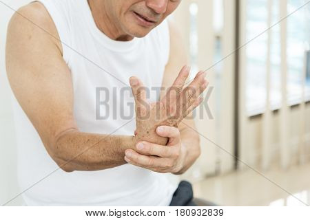 Asian senior man having wrist pain or injury from workout.