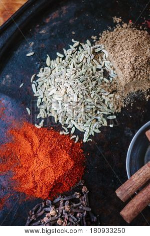 Set Of Spices - Chili Powder, Cloves, Curry Leaves And Caraway Over Black Surface.