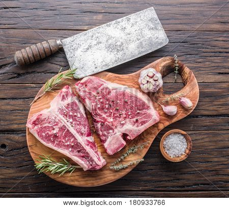 Steak T-bone with spices on the wooden cutting board.