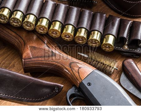 Hunting equipment - pump action shotgun, 12 caliber hunting cartridge  and hunting knife on the wooden table.