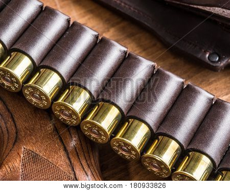Hunting equipment - pump action shotgun, 12 caliber hunting cartridge  and hunting knife on the wooden table. poster