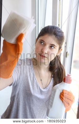 Teen Girl In Orange Rubber Gloves Cleaning Window