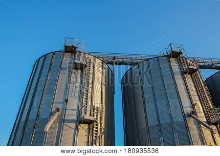 Agricultural Silos Against Blue Sky. Steel grain silos used to store grain.