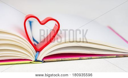 Red heart over diary book on white table. Front short, bright colours